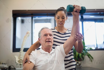 Female doctor looking at senior patient lifting dumbbell