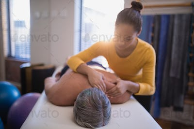 Shirtless male patient lying on bed receiving neck massage from female therapist