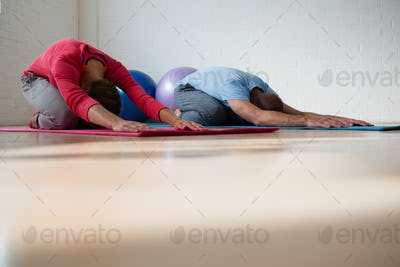 Instructor with student practicing child pose in yoga studio