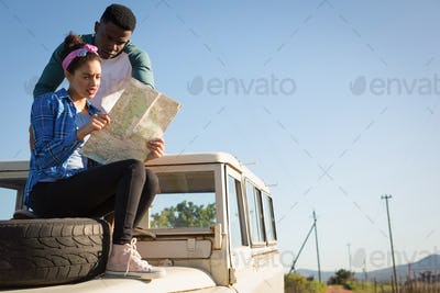 Couple looking at map while sitting on car bonnet