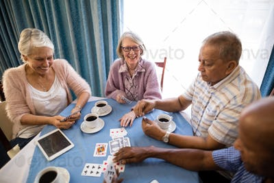 High angle view of senior friends playing cards