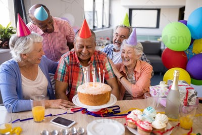 Cheerful friends looking at senior man in birthday party