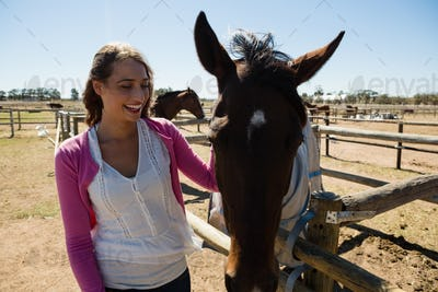 Smiling woman with horse at ranch