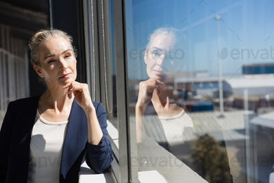Thoughtful businesswoman looking through window at office