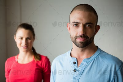Portrait of yoga instructor with student standing in studio