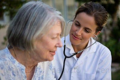 Female doctor examining senior woman with stethoscope
