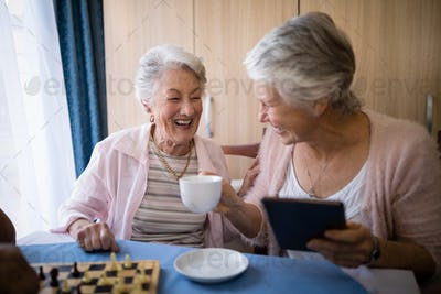 Happy senior friends talking while having coffee