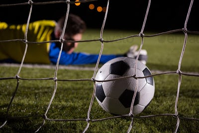 Close-up of soccer ball in goal post against goalkeeper
