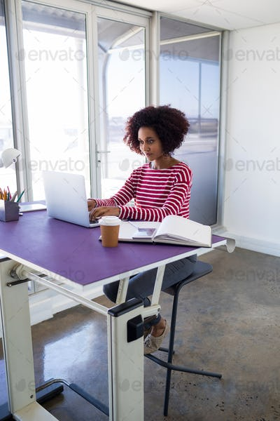 Female executive working over laptop