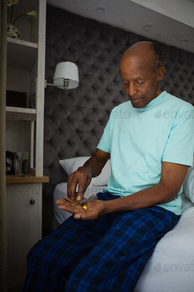Senior man holding medicines while sitting in bedroom at home