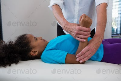 Physiotherapist giving hand massage to a girl patient