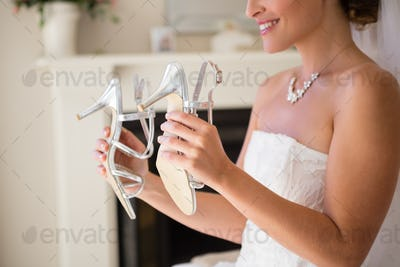 Midsection of smiling bride holding sandals in fitting room