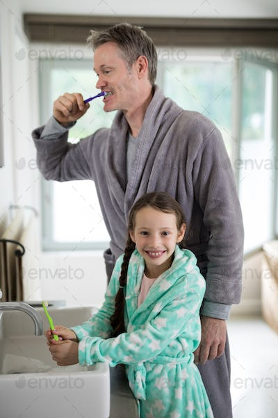 Father and daughter brushing teeth in bathroom