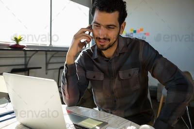Man talking on phone while looking at laptop
