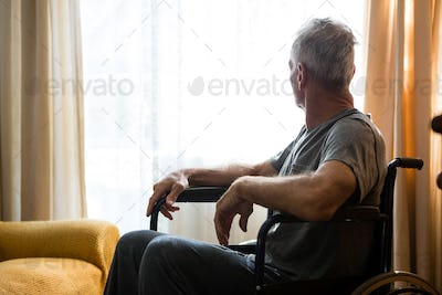 Senior man looking away while sitting on wheelchair