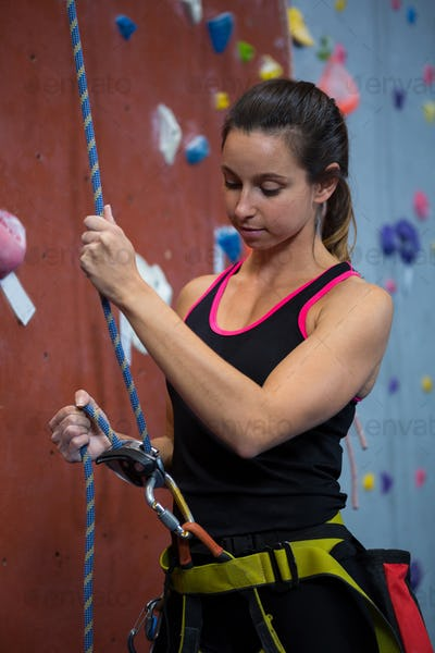 Woman preparing for rock climbing in fitness studio