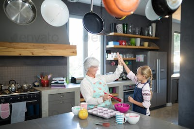 Smiling grandmother and granddaughter giving a high five