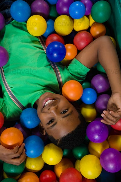 Overhead view of happy boy in ball pool
