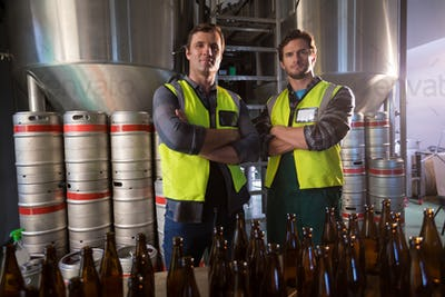 Portrait of coworkers with arms crossed standing by beer bottles