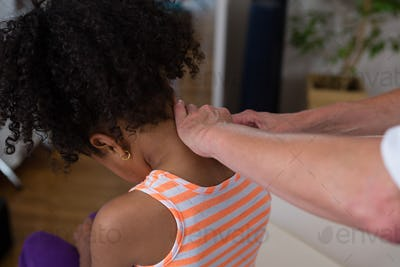 Physiotherapist giving neck massage to girl patient