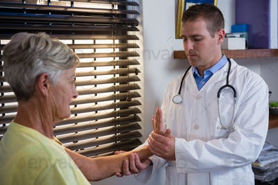 Physiotherapist examining senior patient hand