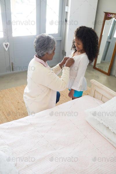 Grandmother dressing up her granddaughter in bedroom