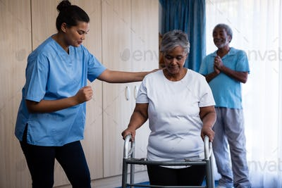 Nurse assisting senior woman in walking with walker