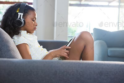 Side view of girl listening music while using tablet computer