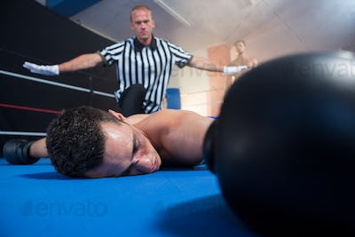 Referee gesturing with arms outstretched by unconscious male boxer