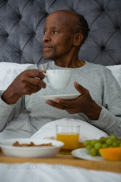 Thoughtful senior man looking away while having breakfast on bed