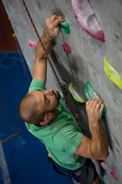 High angle view of confident athlete climbing wall in health club