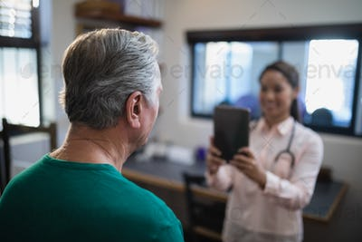 Rear view of senior male patient being photographed by female therapist