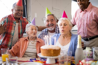 Friends looking at senior woman blowing birthday candles