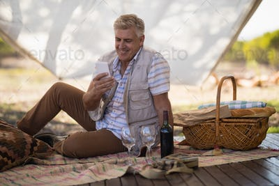 Happy man using mobile phone in cottage