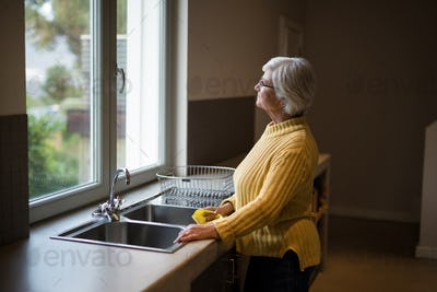 Senior woman standing near the kitchen sink and looking through window