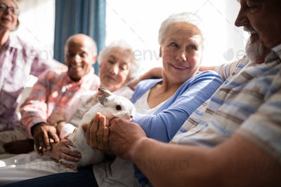 Senior woman holding rabbit while sitting with friends