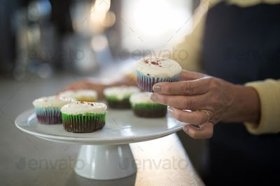 Senior woman picking up the cupcake from the tray