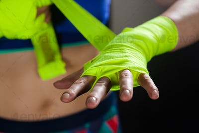 Mid section of woman tying hand wrap on hand