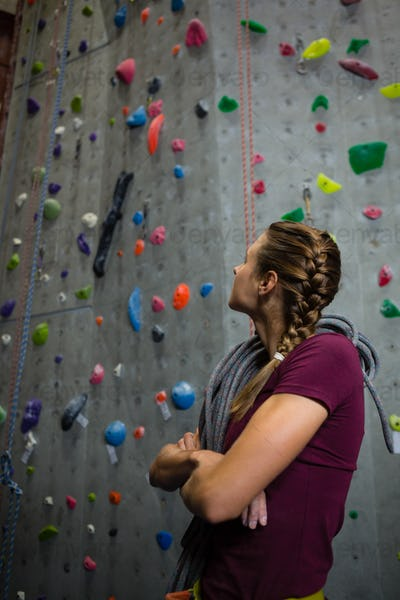 Athlete with rope looking up while standing by climbing wall in club