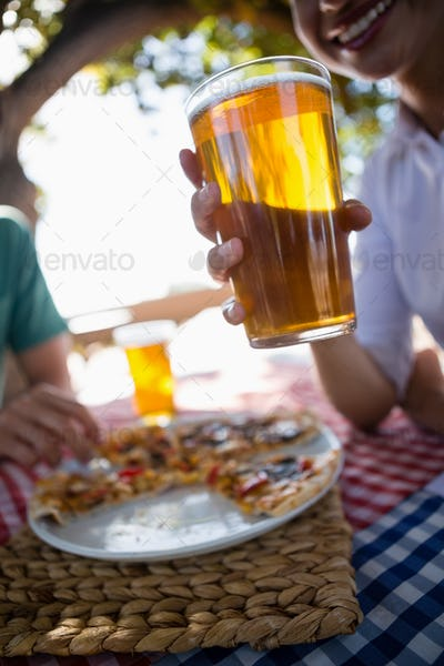 Cropped image of woman holding beer glass