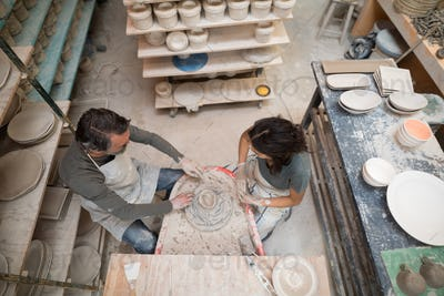 Overhead of male potter assisting female potter