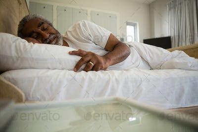 Senior man sleeping on bed in the bedroom