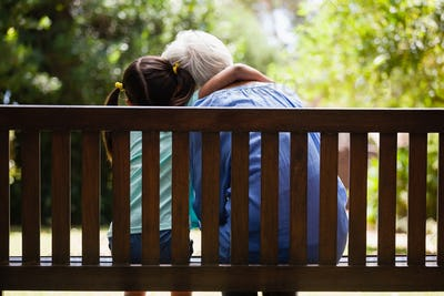 Rear view of granddaughter with arm around grandmother sitting on wooden bench