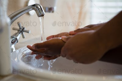 Cropped image of people washing hands in bathroom sink