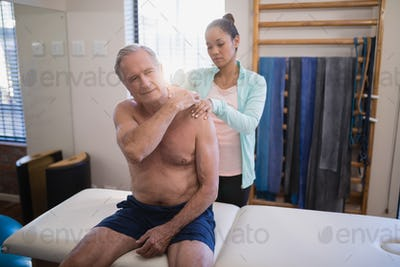 Shirtless senior male patient sitting on bed receiving neck massage from female therapist