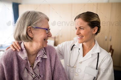 Smiling female doctor looking at senior woman with arm around