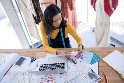 Female designer working on pieces of clothes