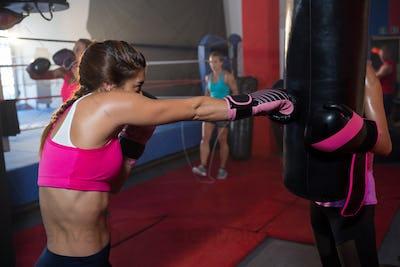 Young female boxer punching black bag