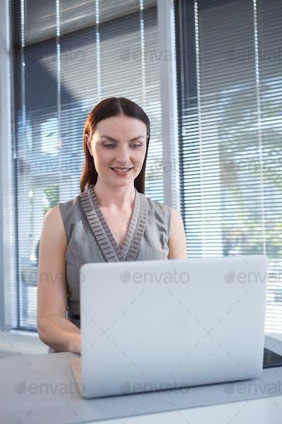 Female executive using laptop at desk