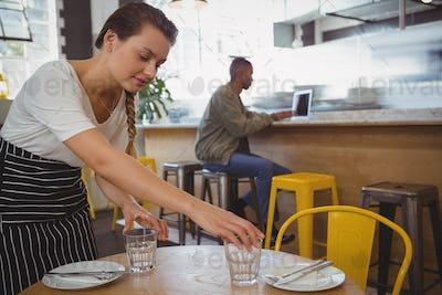 Waitress arranging glasses with businessman using laptop